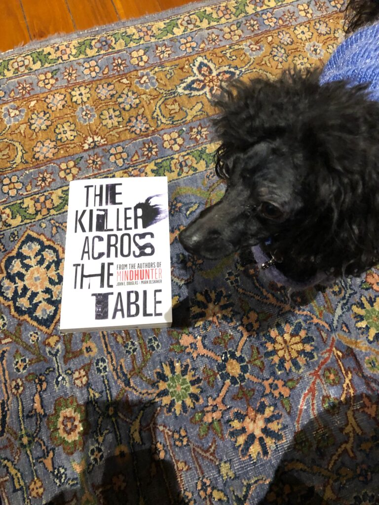 "A picture of my dog Rosie wearing her purple pajamas with the book ""The Killer Across the Table"""