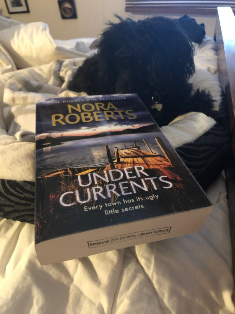 "A picture of my dog, Rosie, in her bed, with the book ""Under Currents"" by Nora Roberts"