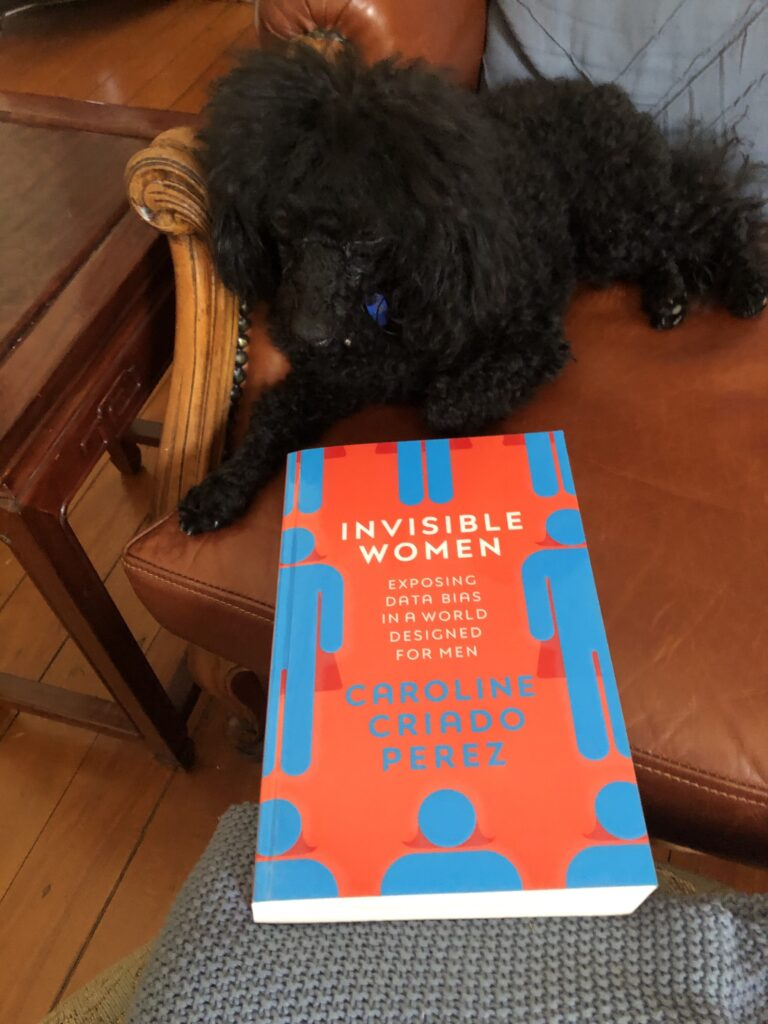 "Rosie the black poodle with the book ""Invisible Women"" by Caroline Criado Perez"